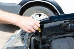 Ręka auto mechanik sprawdza nafcianego poziom z narzędziem zdjęcie royalty free