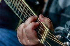 Ręka bawić się czarną gitarę Obrazy Royalty Free