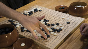 Ręka bawić się czarny i biały kamiennych kawałki na chińczyku Iść lub Weiqi gry deska Salowa aktywność z sztucznym światłem Fotografia Royalty Free