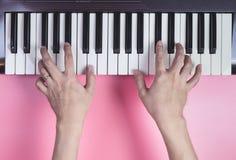 Ręka bawić się Muzyczną klawiaturę na różowym tle Zdjęcia Stock