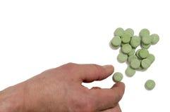 Ręka bierze zielone pigułki Fotografia Stock