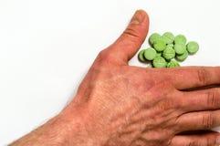 Ręka bierze zielone pigułki Obrazy Stock