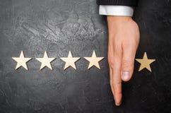Ręka biznesmen oddziela kwinty gwiazdę od inni cztery Strata kwinty gwiazda spadek w ocenie Obrazy Stock