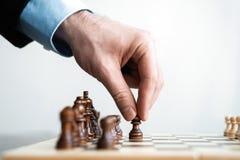 ręka biznesmen poruszająca szachowa postać w turniejowej sukces sztuce strategii, zarządzania lub przywódctwo pojęcie, zdjęcia royalty free