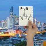 Ręka biznesmen trzyma papierową notatkę z zyskiem i Lin Obrazy Stock