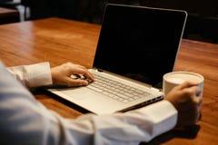 ręka biznesmena chwyta filiżanka z kawą i inny wręczamy pisać na maszynie o Zdjęcia Stock