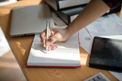 Ręka biznesmena mienia pióro podczas gdy pisać notatce w książce obraz royalty free