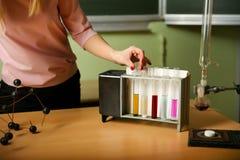 r?ka chemia nauczyciel wyci?ga pr?bnej tubki z barwionym cieczem zdjęcia stock