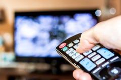 Ręka chwyt pilot do tv zmieniać kanały na Tv obraz stock