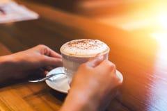 Ręka chwyta łyżka w naczyniu i filiżanka kawy zdjęcie royalty free