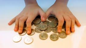 Ręka chwyta monety dla pieniężnych i oszczędzania pojęć, oszczędzanie pieniądze Obrazy Stock