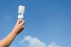 Ręka chwyta niebieskiego nieba energooszczędny lampowy tło Fotografia Stock
