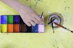 Ręka chwyta paintbrush stawiający w kolor tacy zawiera różnorodnego koloru dowcip Zdjęcie Royalty Free