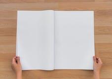 Ręka chwyta Pusta gazeta z pustym przestrzeń egzaminem próbnym up na drewnianym backg Zdjęcia Royalty Free