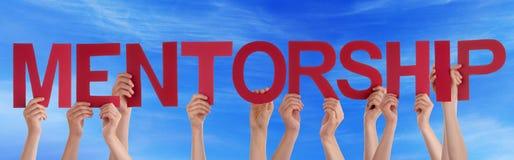 Ręka chwyta słowa mentorstwa Czerwony Prosty niebieskie niebo Obraz Stock