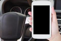 Ręka chwyta telefon komórkowy z samochodową kierownicą Obrazy Stock
