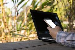 Ręka chwyta telefonu komórkowego egzamin próbny up na ekranie nad laptopem, biznes fotografia stock