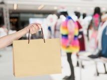 Ręka chwyta torba na zakupy z plama sklepem odzieżowym Fotografia Stock