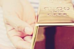Ręka chwyta złociści bary Fotografia Royalty Free