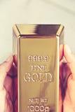 Ręka chwyta złociści bary Obraz Stock