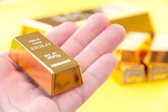 Ręka chwyta złociści bary Zdjęcia Stock