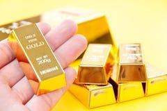 Ręka chwyta złociści bary Obraz Royalty Free