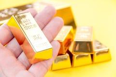 Ręka chwyta złociści bary Zdjęcia Royalty Free
