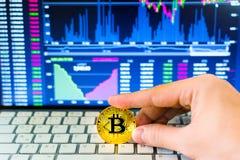 Ręka chwyta złocisty bitcoin i handel sporządzamy mapę tło Wirtualny waluty pojęcie Obraz Stock