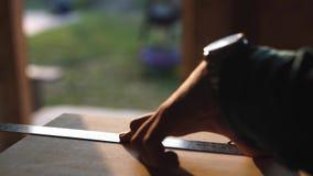 Ręka cieśla bierze pomiar drewniana deska słońce racy ob tło zbiory wideo