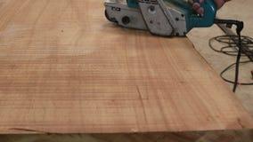 Ręka cieśla używa pasowego sander z drewnianą deską w warsztacie zdjęcie wideo