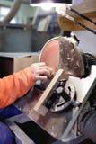 Ręka czyści drewnianego blok na maszynie fotografia stock