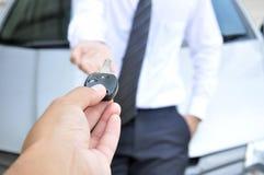 Ręka daje samochodowemu kluczowi - samochodowa sprzedaż & wynajem usługa Obrazy Royalty Free