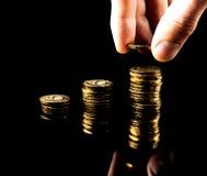 Ręka dostarcza stertę moneta wykresu zysku przyrost na czarnym tle Zdjęcia Stock