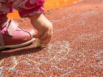 Ręka dziecka mali remisy pisze kredą fotografia royalty free