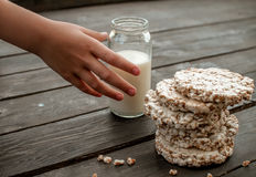 Ręka dziecko bierze do domu mleko smakowity crispbread na drewnianym tło stole Obraz Royalty Free