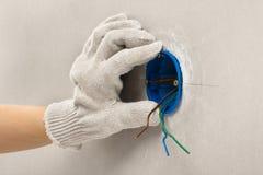 Ręka elektryk w rękawiczkowym instaluje plastikowym ujścia pudełku zdjęcie royalty free