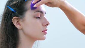Ręka fachowy makijażu artysta stosuje tonalną śmietankę lub remedium używać gąbkę zbiory wideo