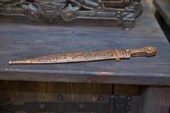 Ręka forged pirata kord, elegancka broń od brutalnego wieka Miedziany kordzik na drewnianym tle fotografia royalty free