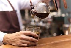 Ręka kapinos spuszcza kawę, Barista dolewanie warząca kawa w cu zdjęcie stock