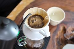 Ręka kapinosa kawa Zmielone kawowe fasole w tapetują filtr z gorącą wodą Obraz Royalty Free