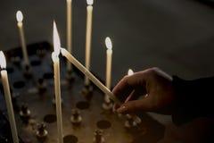 Ręka kobiet oświetleniowe świeczki w kościół Zdjęcie Royalty Free