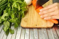 Ręka kobiet tnące marchewki warzywa na drewnianej desce i obraz royalty free