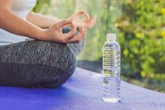 Ręka kobieta medytuje w joga pozie na dywaniku dla joga i butelce woda obraz royalty free