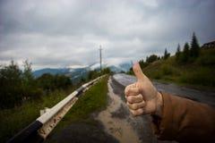 Ręka kobieta podróżnik z aprobatami na asfaltowej drodze iść podróżować Fotografia Stock