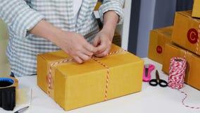 Ręka kobieta przedsiębiorca wiąże arkany i pakujący produkty w pakuneczka pudełku, przygotowywa dla dostawy klienci w ministerstw zbiory