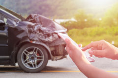Ręka kobieta używa smartphone i plama jej łamany samochodowy parkin Fotografia Royalty Free