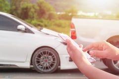 Ręka kobieta używa smartphone i plama jej łamany samochodowy parkin Zdjęcia Stock