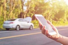 Ręka kobieta używa smartphone i plama jej łamany samochodowy parkin Obraz Royalty Free
