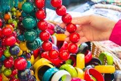Ręka kobieta z drewnianą kolią na kramu przy bazarem Obrazy Stock