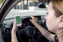 Ręka kobiety mienia kierownica i telefonu komórkowego napędowy samochód podczas gdy texting rozpraszam uwagę w ryzyku Zdjęcia Royalty Free
